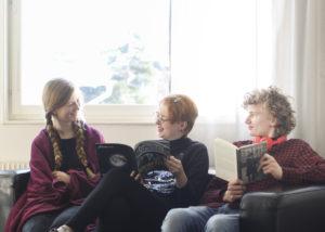 Tre elever sitter i soffa
